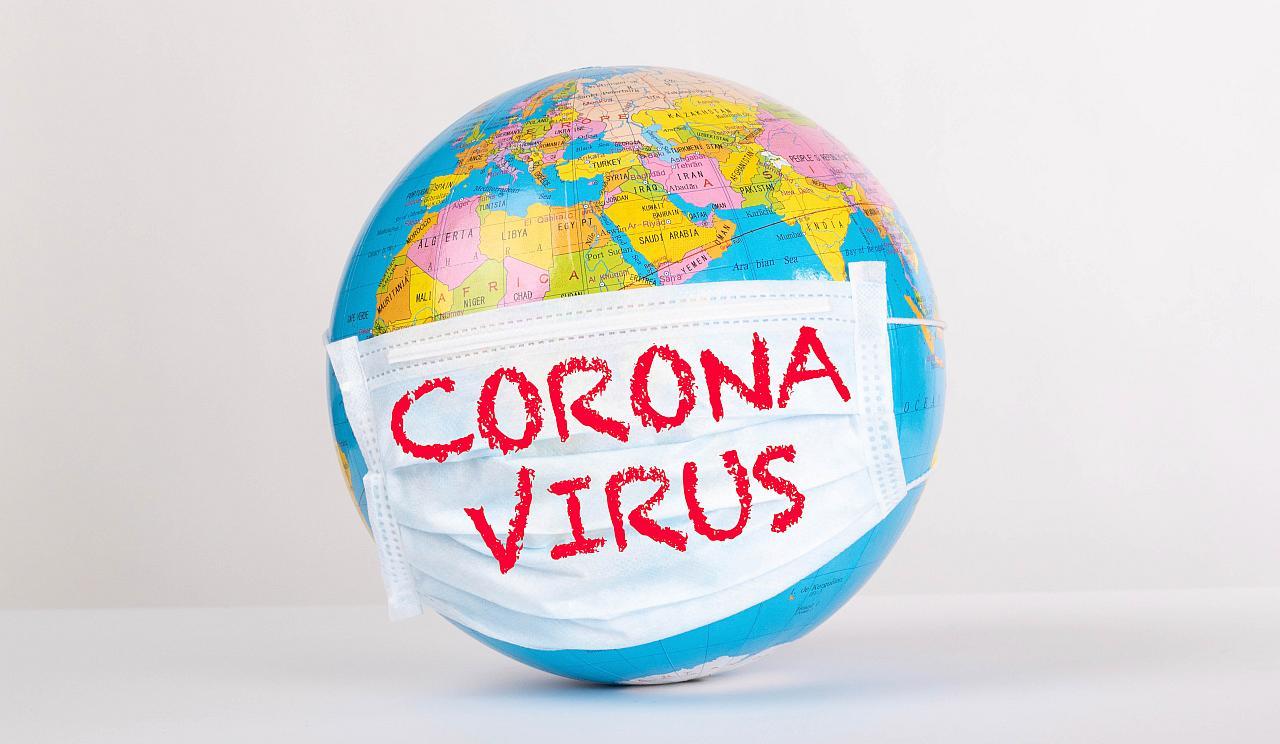 Eine Weltkugel mit Gesichtsschutz auf dem Corona Virus geschrieben steht.