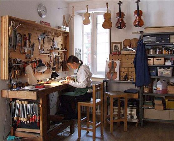 Blick in eine Geigenbauerwerkstatt. Eine Geigenbaumeisterin arbeitet an einem Instrument.