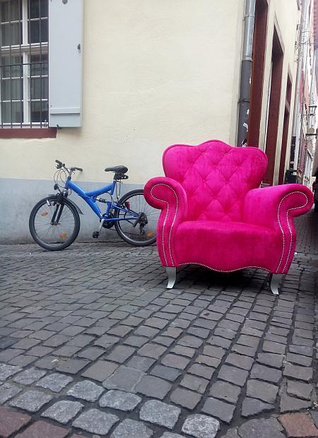 Ein schicker Sessel in grellem Rosa steht auf dem Kopfsteinpflaster