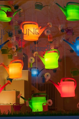 Foto eines Schaufensters, Gespickt mit bunten, hängenden gießkannen, die als Lampen fungieren