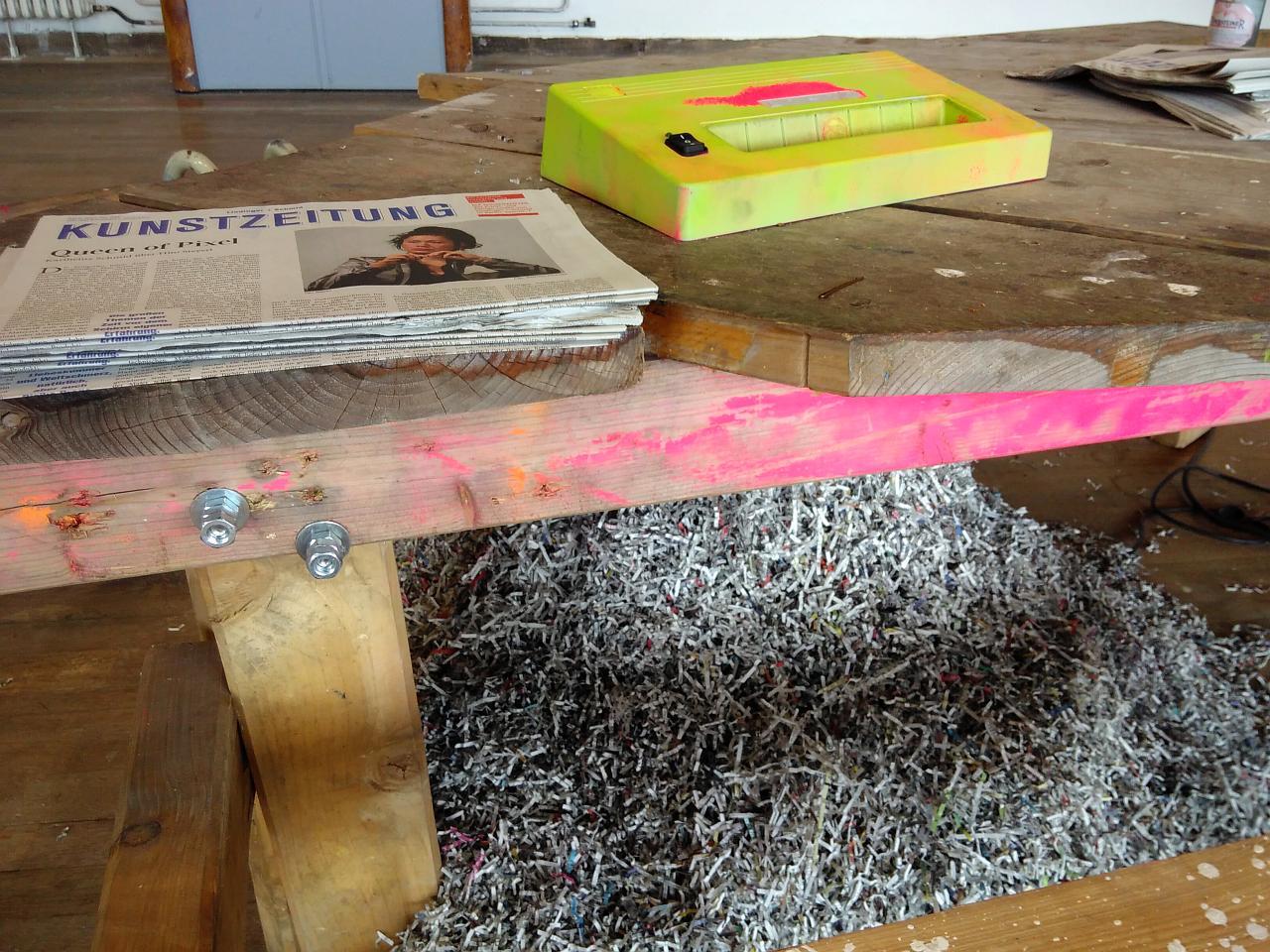 In einen Tisch ist ein Papiershredder eingebaut und in neongelb angemalt. Darunter ist ein Berg geshreddertes Papier sichtbar. Danaben liegt ein Stapel der Kunstzeitung.